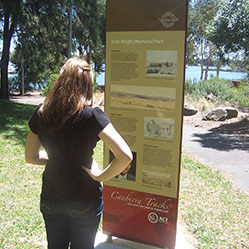 Woman looking at interpretive sign on Track 6, Belconnen