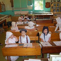 Children in period dress inside the Ginninderra Schoolhouse